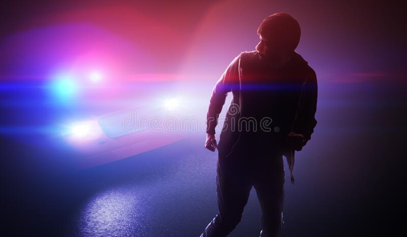 Silhouette of young man - thief escaping from police car at night. stock photo