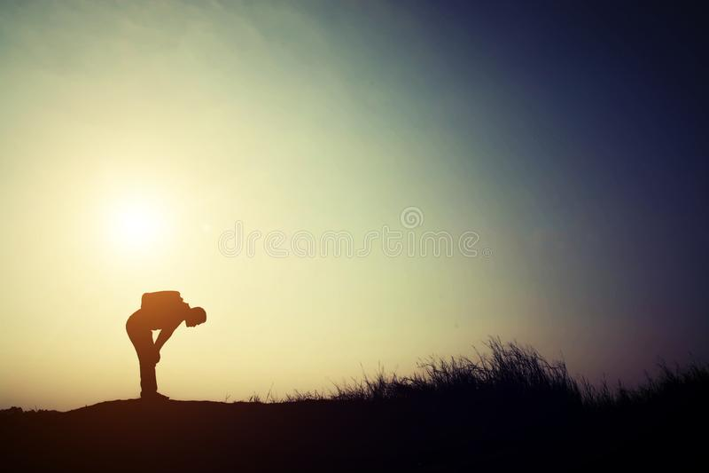 Silhouette of young man tired for walking alone with his backpack. royalty free stock photo