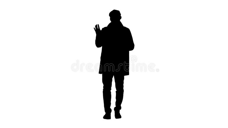 Silhouette Young man in trench coat makes hi gesture. royalty free stock photo