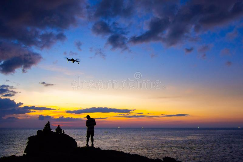 Silhouette of young man using and watching a flying drone in twilight sky over the sea for photos or video making royalty free stock photos