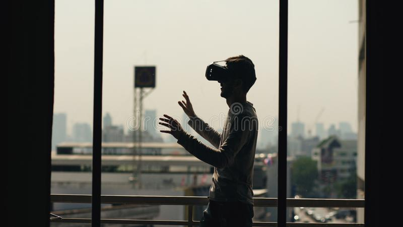 Silhouette of young man watching movie in VR headset and have virtual reality experience on hotel room balcony stock images