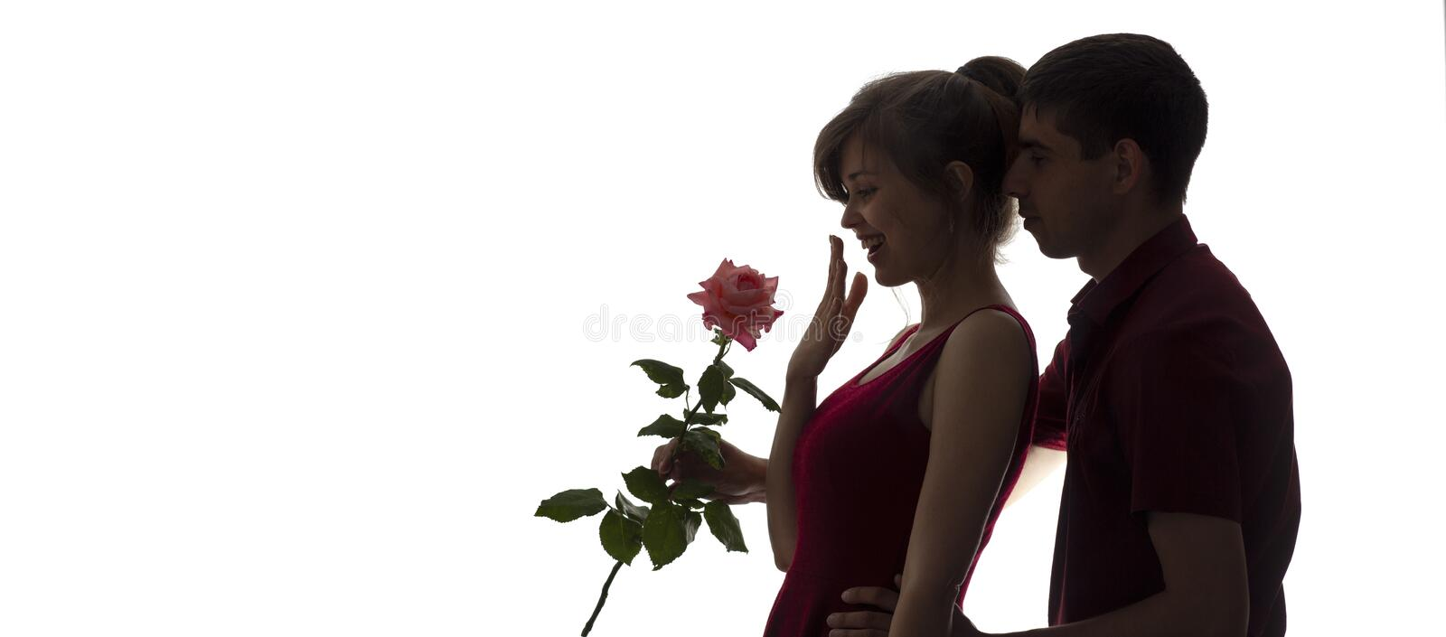 Silhouette of a young man and woman in love on white isolated background, boy came up behind to girl to make a surprise with rose stock image