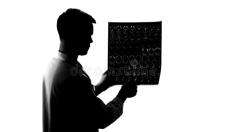 Silhouette of young neurologist examining mri results, brain disease, occupation royalty free stock images