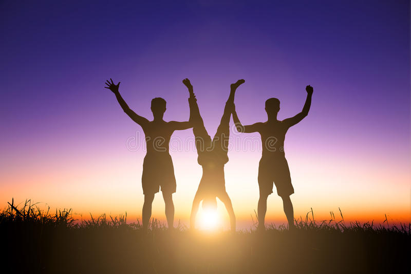 The Silhouette of young people catching a handstand person stock image