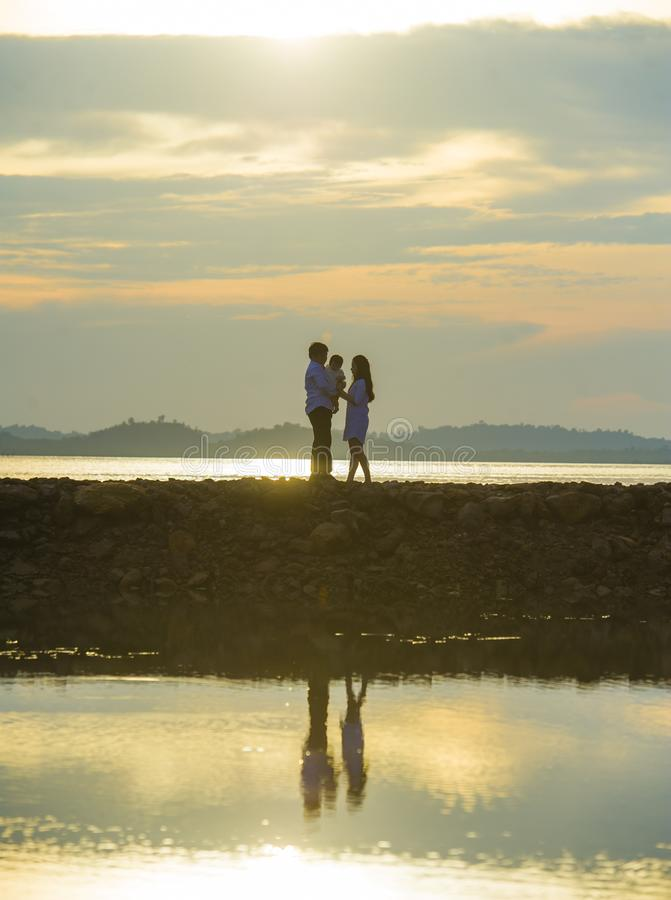 Silhouette of young romantic couple holding and playing with son or daughter little baby enjoying sunset having a walk at beach stock photos
