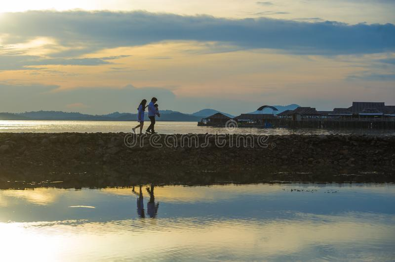 Silhouette of young romantic couple holding and playing with son or daughter little baby enjoying sunset having a walk at beach stock photo