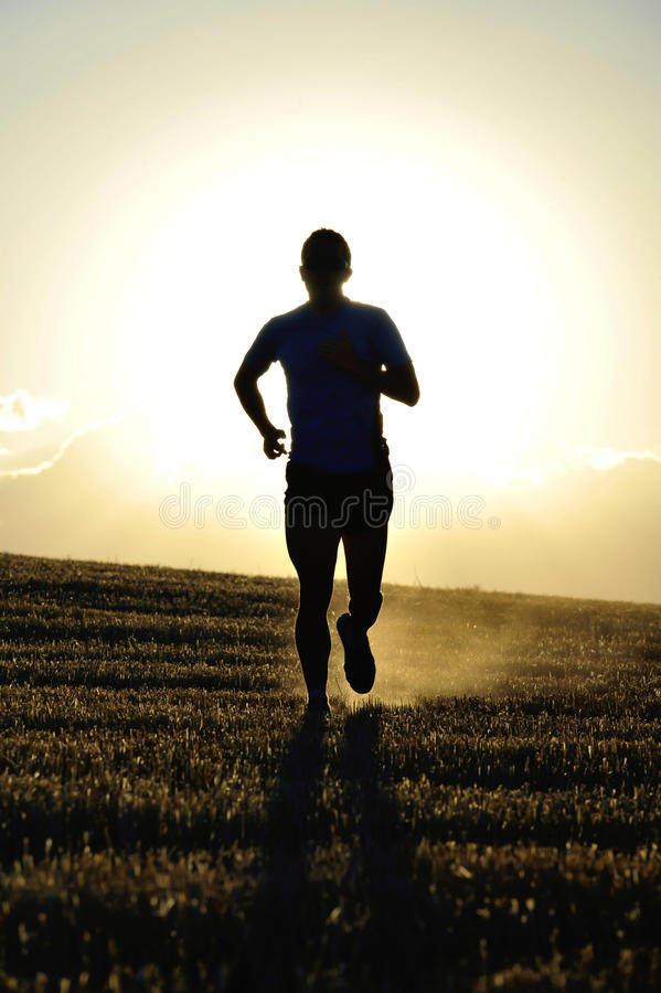 Silhouette young sport man running off road in countryside straw field backlight at summer sunset stock photo