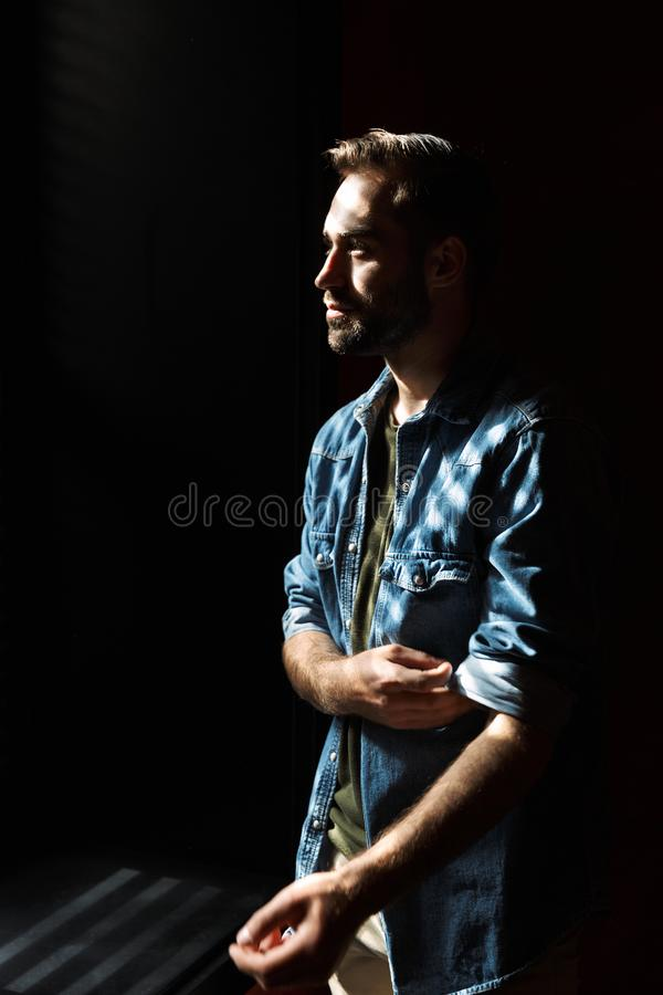 Silhouette of young thoughtful man standing in dark room at shadow blinds. Silhouette of young thoughtful man standing in dark room against the sunlight from royalty free stock photo