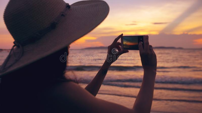 Silhouette of young tourist woman in hat taking photo with cellphone during sunset in ocean beach stock image