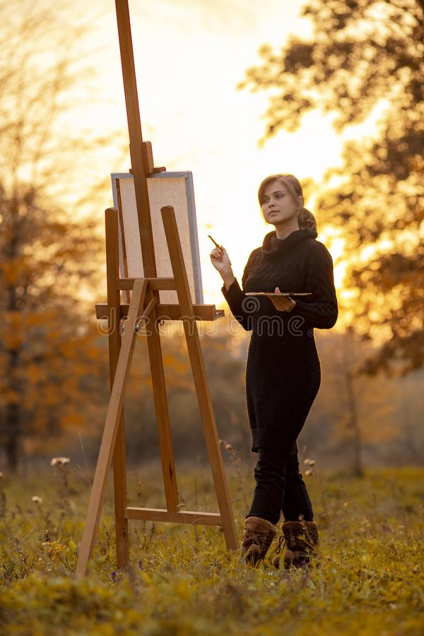 Silhouette of young woman artist painting a picture on the easel, girl figure with a brush and a palette of colors on the stock photo