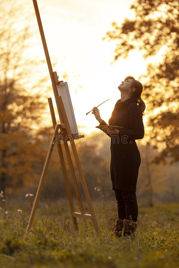Silhouette of young woman artist painting a picture on the easel, girl figure with a brush and a palette of colors on the stock photography