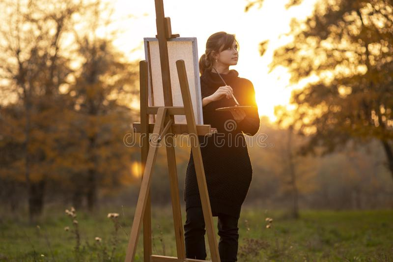 Silhouette of young woman artist painting a picture on the easel, girl figure with a brush and a palette of colors on the royalty free stock photography