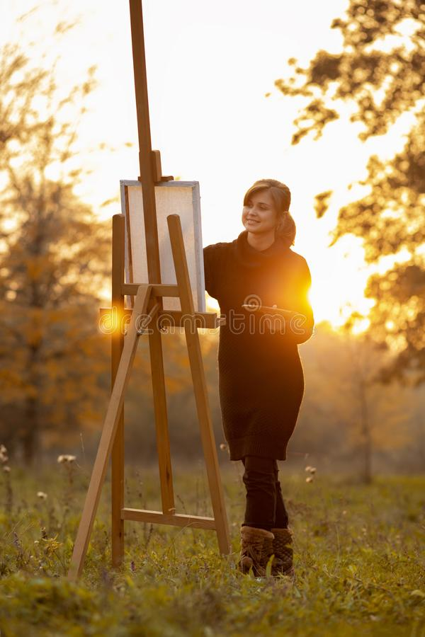 Silhouette of young woman artist painting a picture on the easel, girl figure with a brush and a palette of colors on the stock image