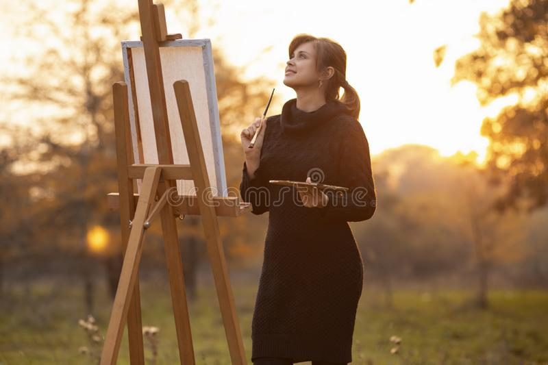 Silhouette of young woman artist painting a picture on the easel, girl figure with a brush and a palette of colors on the royalty free stock photos