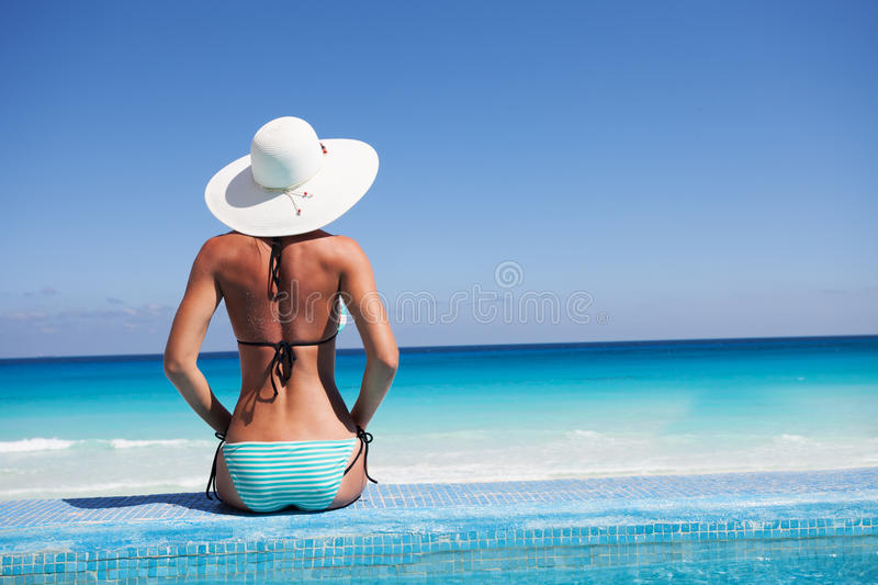 Silhouette of young woman on beach with hat. Silhouette of young woman on beach with white hat from the back stock photo