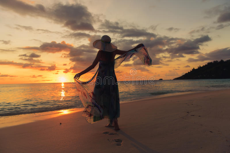 Silhouette young woman on the beach at sunset stock photo