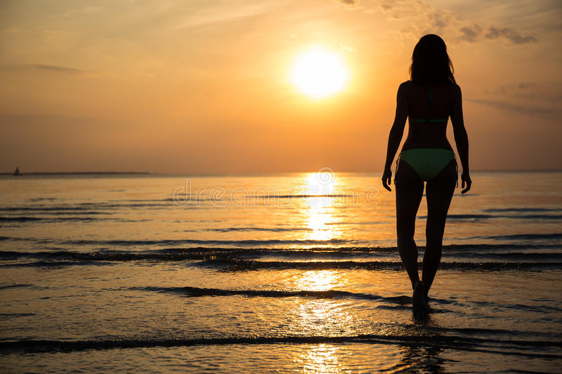 Silhouette of young woman in bikini walking on beach at sunset stock photos