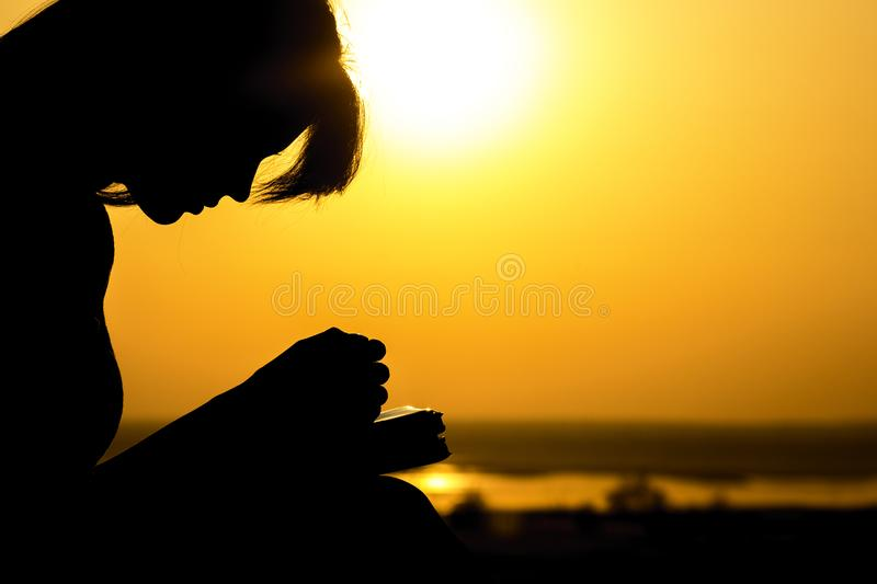 Silhouette of the hands of woman praying to God in the nature witth the Bible at sunset, the concept of religion and spirituality royalty free stock images