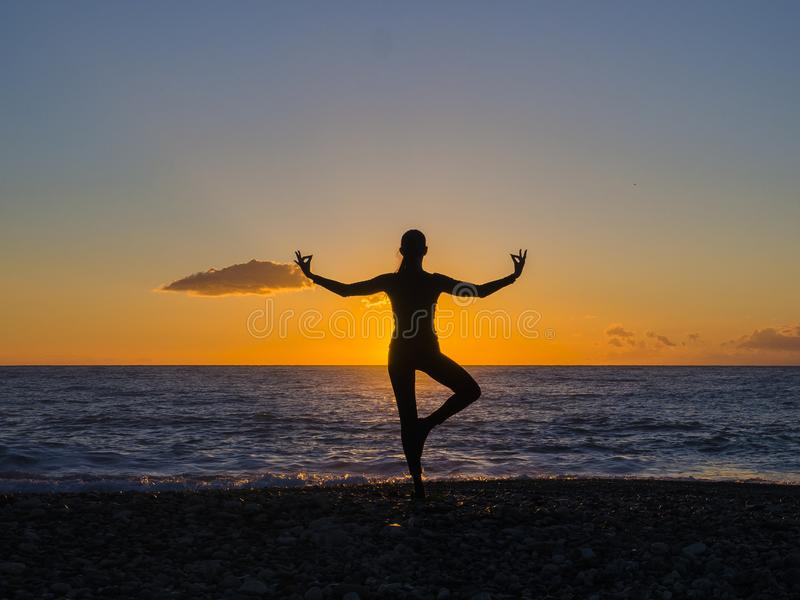 Silhouette of young woman doing exercises on the sea beach during sunset. Yoga, fitness and a healthy lifestyle stock photography