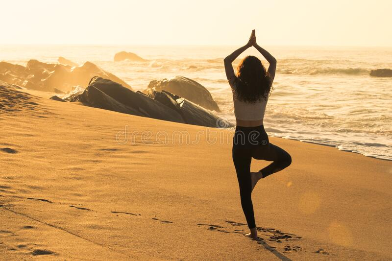 Silhouette of young woman doing greeting the sun yoga asana on the beach stock image