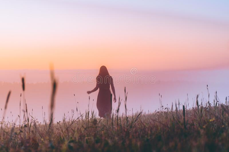 Silhouette young woman in a dress walking on a hill on sunrise. female running on a foggy field and enjoying forest landscape. Act. Ive life, adventure, freedom stock photo