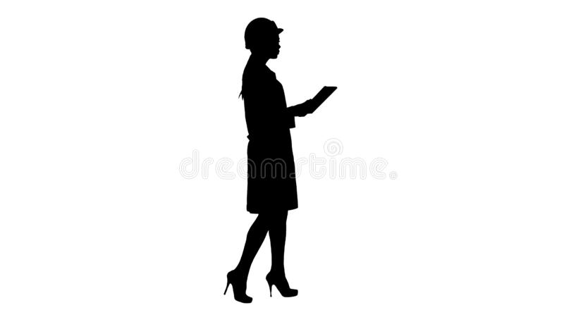Silhouette Young woman engineer walking with tablet looking at objects around. stock photos