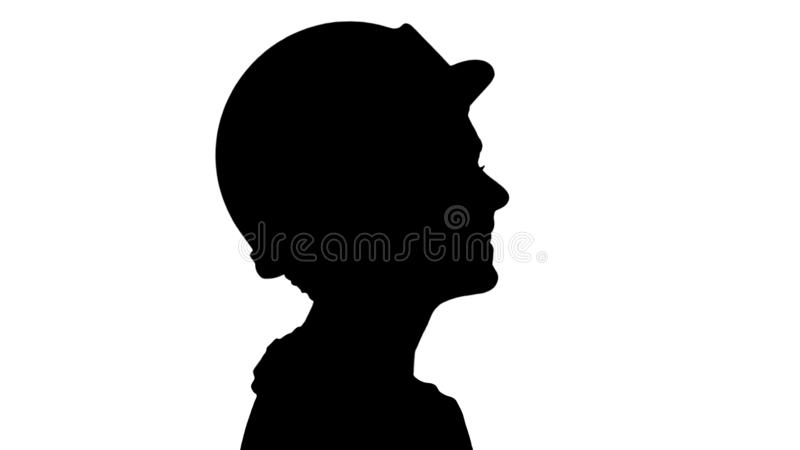 Silhouette The young woman engineer with yellow safety helmet walking and smiling. royalty free stock image