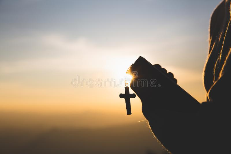 Silhouette of Young woman hands holding holy Bible and lift of christian cross, religion symbol in light and landscape over a royalty free stock photography