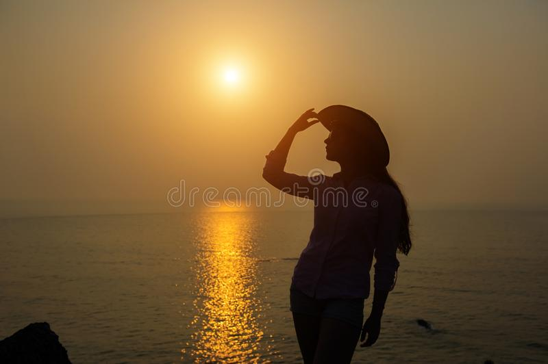 Silhouette of young woman in a hat against sunset over the sea. Beautiful slender girl enjoys peace and relaxation on the ocean royalty free stock photos