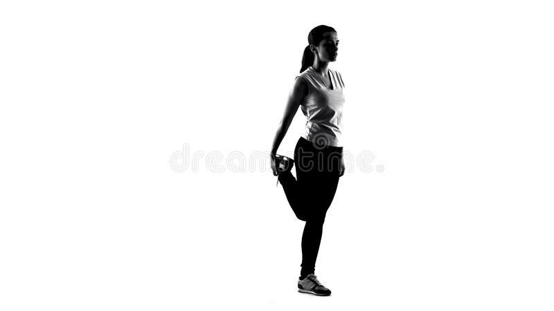 Silhouette of young woman making yoga exercises and meditating, sport healthcare royalty free stock image