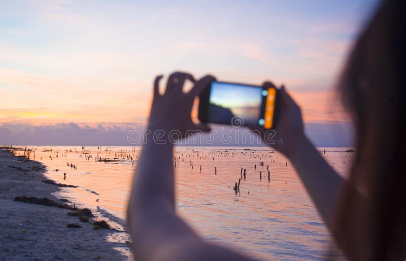 Silhouette of young woman with mobile phone camera taking picture of beautiful beach sunset landscape and mount Agung volcano of B stock image