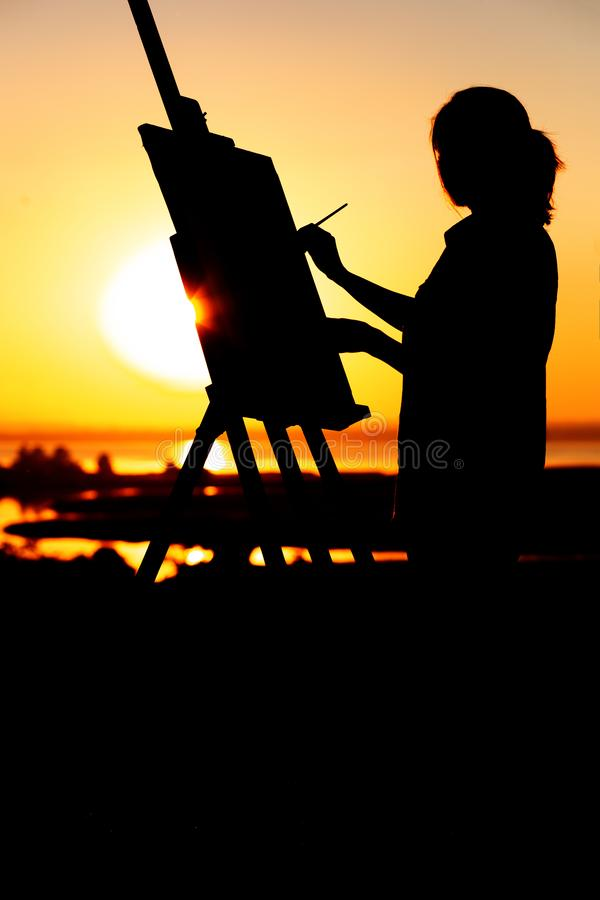 Silhouette of a young woman painting a picture on an easel on nature, girl figure with brush and artist`s palette engaged in art royalty free stock image