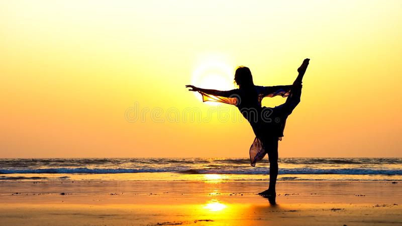 Silhouette of young woman performing rhythmic gymnastics element on the beach stock images