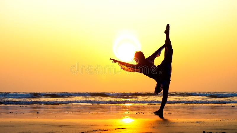 Silhouette of young woman performing rhythmic gymnastics element on the beach. Silhouette of young sporty woman performing rhythmic gymnastics element on the stock images