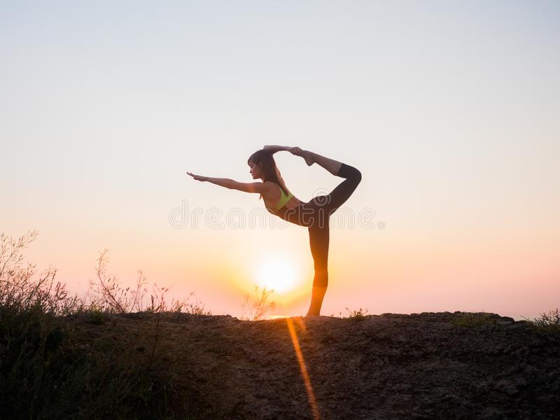 Silhouette young woman practicing yoga on the beach above sea at amazing sunset. fitness, sport, yoga and healthy royalty free stock photography