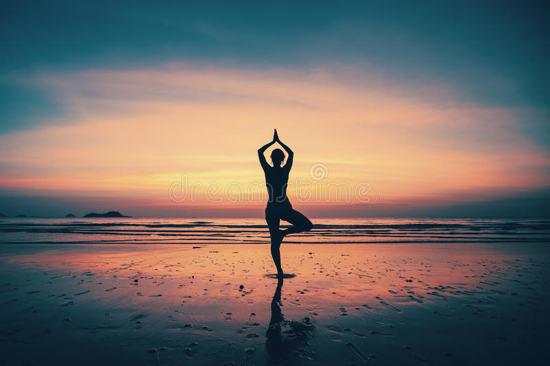 Silhouette young woman practicing yoga on the beach royalty free stock photos