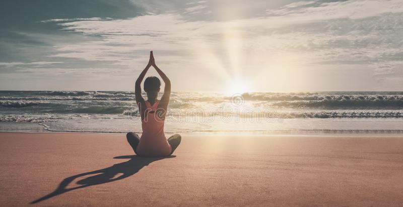 Silhouette young woman practicing yoga on the beach at sunset. Yoga and meditation on the calm peaceful beach at sunset. Fitness a. Nd healthy lifestyle stock photo