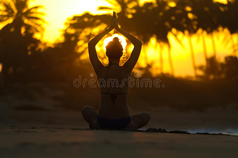 Silhouette of a young woman practicing yoga on the beach at sunset royalty free stock photography