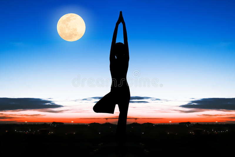 Silhouette young woman practicing yoga stock photography