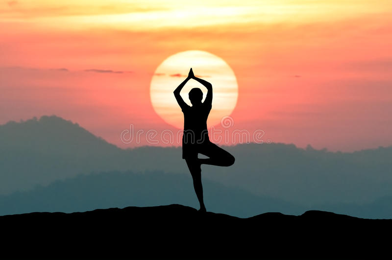 Silhouette young woman practicing yoga on mountain at sunset twilight sky. royalty free stock photo