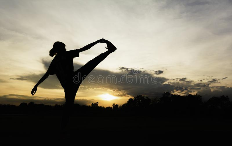 Silhouette of young woman practicing yoga outdoor. Female happiness. Sport and healthy concept stock images