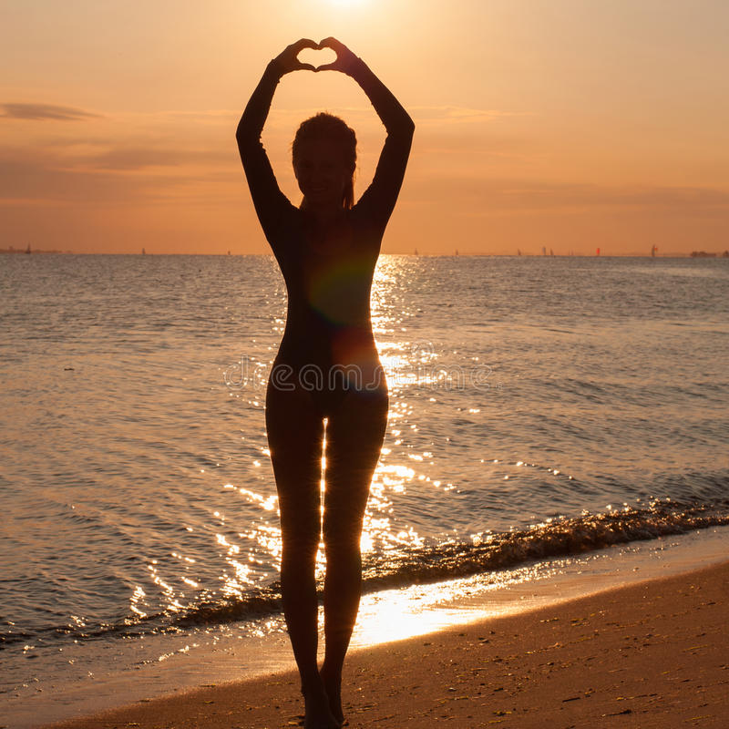 Silhouette of a young woman practicing yoga at the seaside at sunset. Yoga on the beach. Silhouette of a young woman practicing yoga at the seaside at sunset stock photography