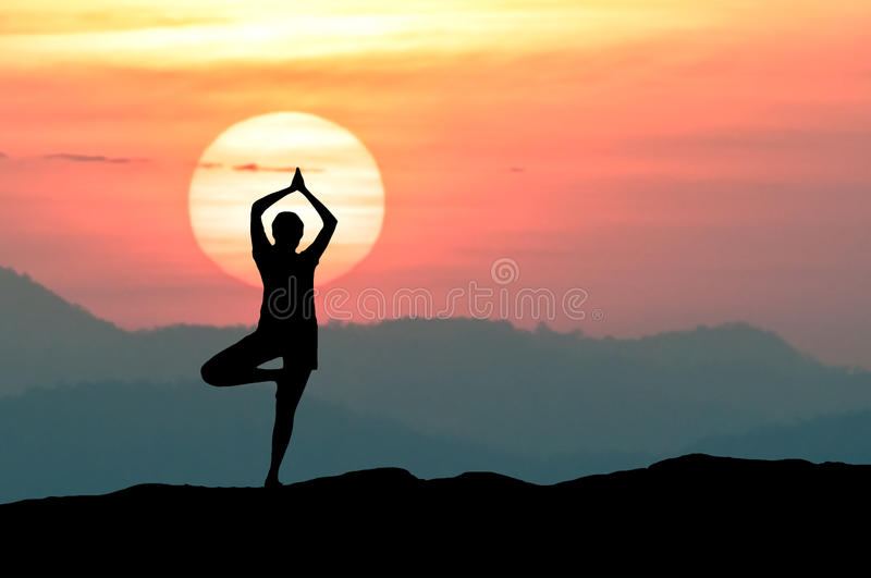 Silhouette young woman practicing yoga with sunrise background royalty free stock photography