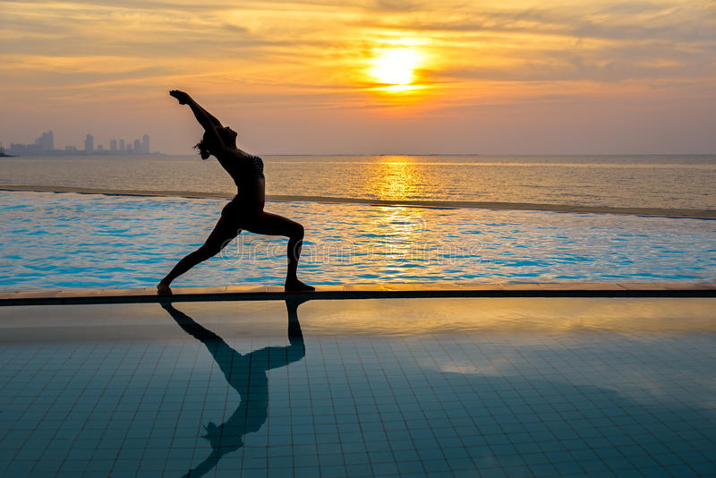 Silhouette young woman practicing yoga on swimming pool and the beach at sunset stock photos