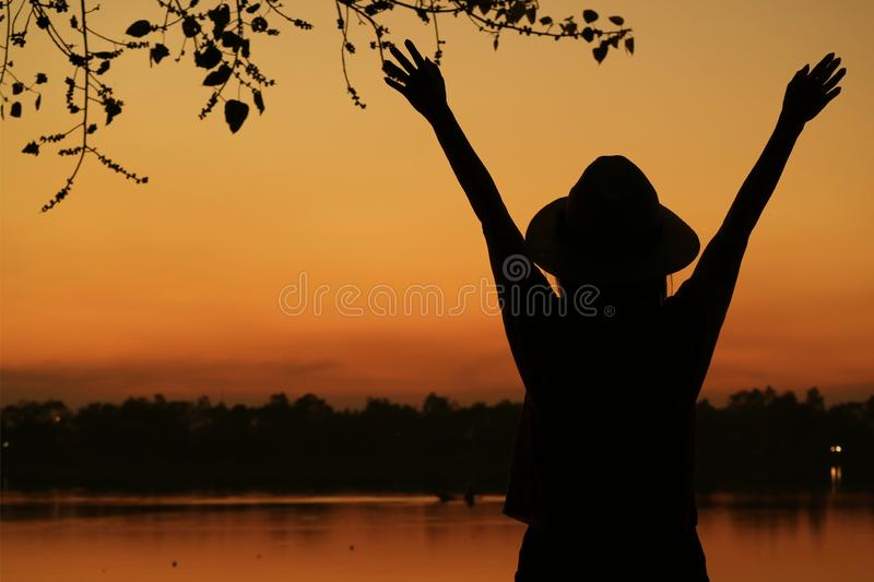 Silhouette of a young woman raising arms against beautiful orange color sunset sky on the lake shore. Beauty in nature dusk evening female forest free freedom royalty free stock photos