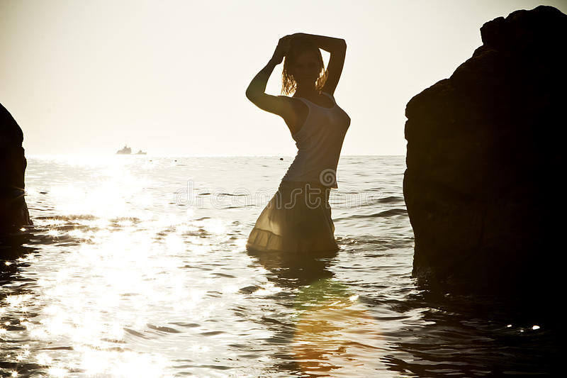 Download Silhouette Of Young Woman In Sea On Sunset Stock Photo - Image: 22518888