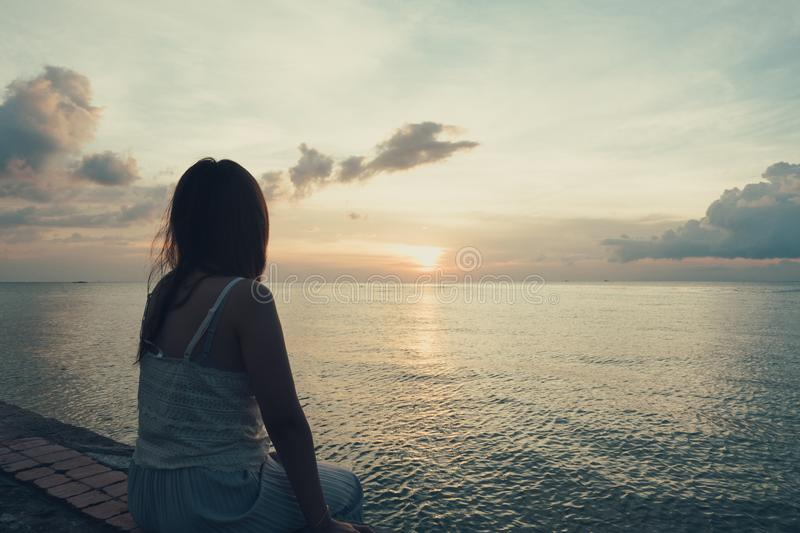 Silhouette of young woman sitting alone on back side outdoor at stock photos
