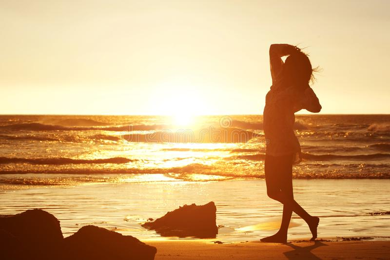 Silhouette of a young woman standing on beach stock photos