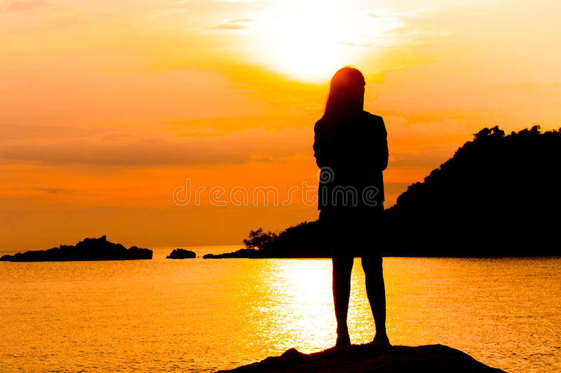 Silhouette of young woman standing at relax pose or freedom pose or chill pose royalty free stock images