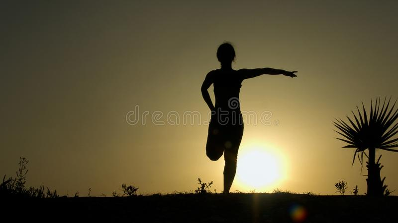 Silhouette of young woman stretching before doing exercises early morning royalty free stock photography